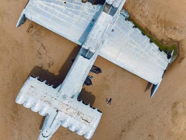 Deux personnes un garçon et son père sont allongées sur le sable à côté d'un écroplan