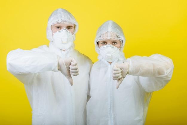 Deux personnes un homme et une femme médecin en tenue de protection individuelle (epi). dans les gants et les masques
