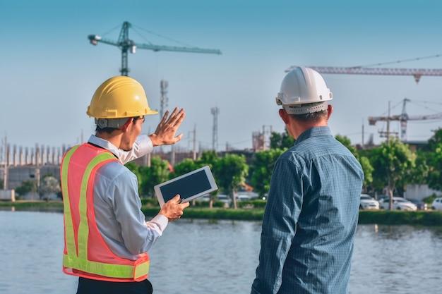 Deux personnes ingénieur travailleur parler discussion par tablette sur la construction de l'immobilier de construction de site