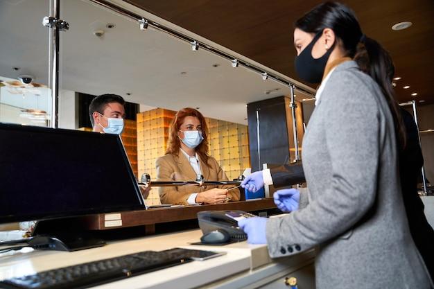 Deux personnes portant des masques médicaux debout derrière un écran de verre dans un hall d'hôtel lors de l'enregistrement