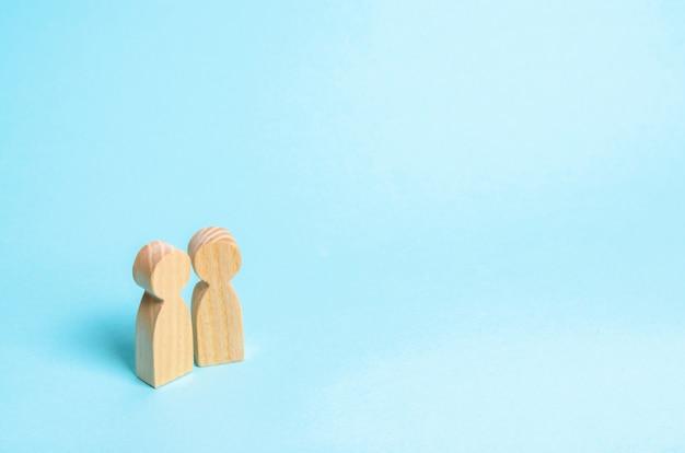 Deux personnes se tiennent ensemble et parlent. conversation de deux personnages en bois