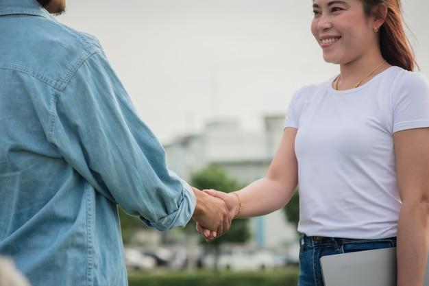 Deux personnes serrent la main amitié en plein air, poignée de main concept
