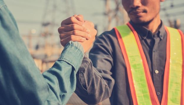 Deux personnes serrer la main partenariat de travail d'équipe ingénieur superviseur contremaître