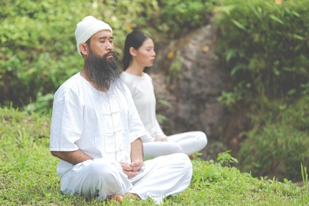 Deux personnes en tenue blanche méditant dans la nature