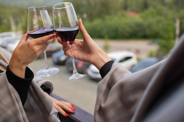 Deux personnes tintant avec des verres de vin rouge, célébrant le succès ou parlant des toasts dans un restaurant à vin, contre des racks avec des bouteilles de vin, se bouchent.