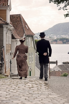 Deux personnes en vêtements anciens dans la rue d'une ville ancienne