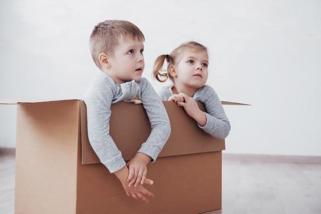 Deux un petit garçon et une fille viennent d'emménager dans une nouvelle maison. concept photo .. les enfants s'amusent.