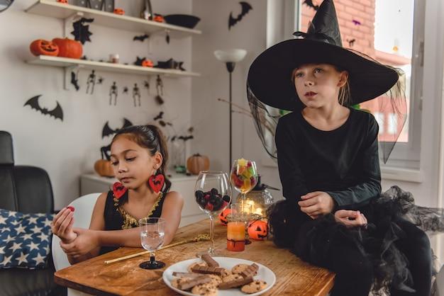 Deux petite fille en costumes manger des bonbons