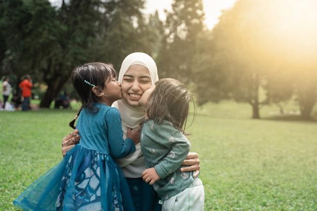 Deux petite fille embrassant sa mère