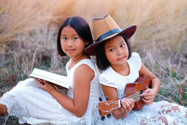 Deux petite fille en robe blanche, jouer au ukulélé avec un chapeau brun
