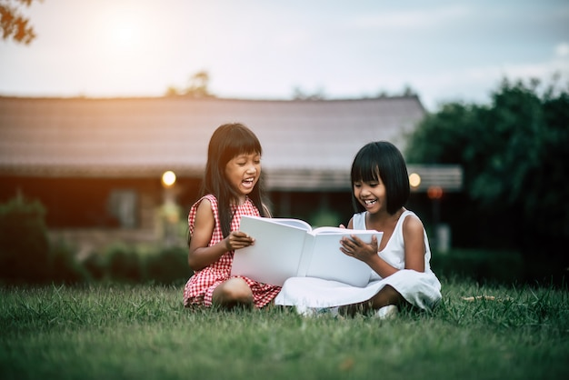 Deux petites amies dans le parc sur l'herbe en lisant un livre et apprendre