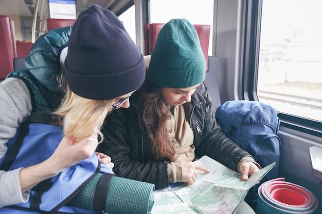 Deux petites amies voyageant avec des sacs à dos et un inventaire vont dans le train et regardent l'itinéraire plus loin sur la carte