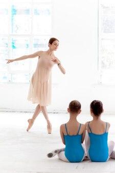 Deux petites ballerines dansant avec un professeur de ballet personnel en studio de danse
