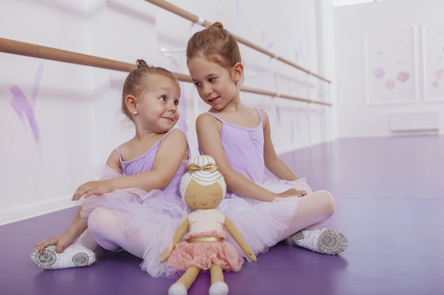 Deux petites ballerines mignonnes assis dos à dos sur le sol, se regardant par-dessus leurs épaules