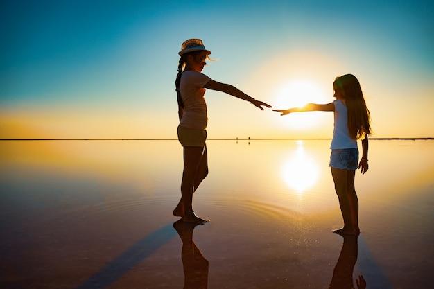 Deux petites belles sœurs heureuses marchent le long du lac salé rose en forme de miroir en profitant du chaud soleil d'été pendant les vacances tant attendues