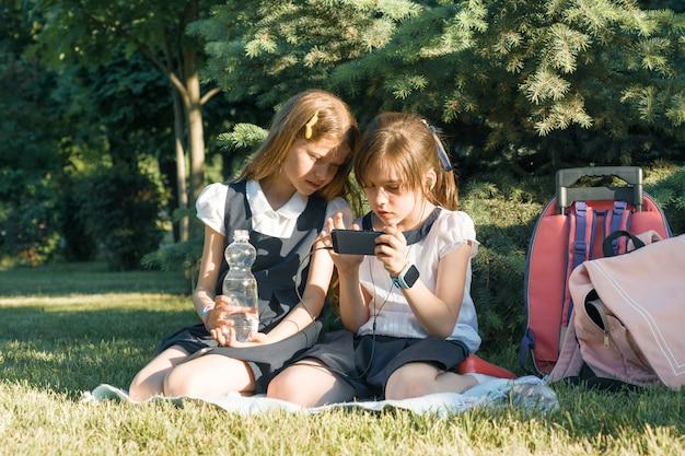 Deux petites écolières à l'aide de smartphone