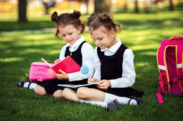 Deux petites écolières portant un sac à dos rose, assises sur l'herbe après les cours et lisant des leçons ou un livre,