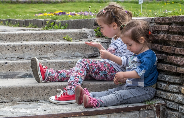 Deux petites filles assises sur les marches à l'extérieur, le concept d'avoir un repos enfants