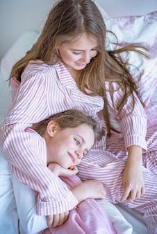 Deux petites filles au lit embrassant. deux petites sœurs parlent le matin au lit.