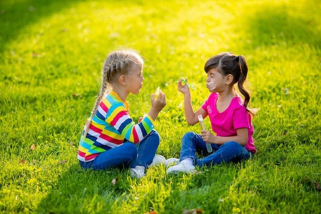 Deux petites filles blondes et brune d'été s'asseoir sur la pelouse soufflant des bulles de savon enfants de l'ethnie européenne et indienne