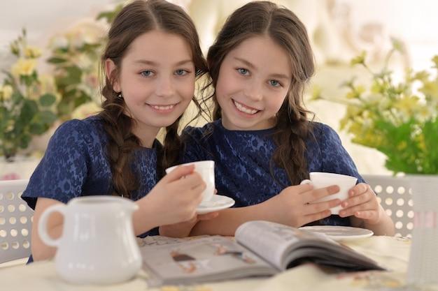 Deux petites filles buvant du thé et lisant un magazine