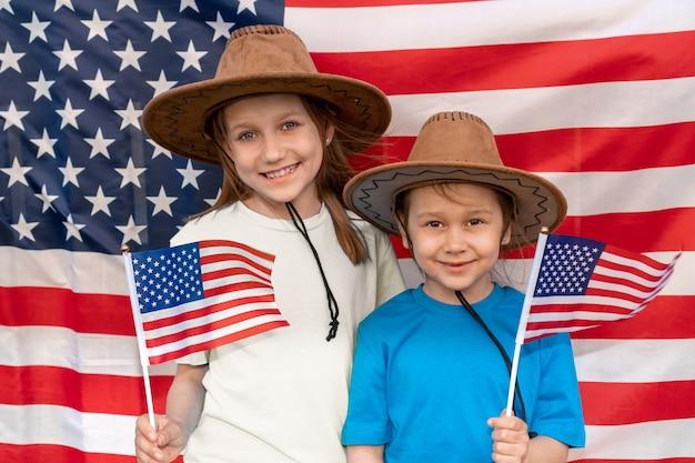 Deux petites filles en chapeaux de cow-boy avec des drapeaux américains dans leurs mains