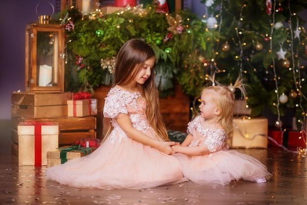 Deux petites filles à côté de l'arbre de noël