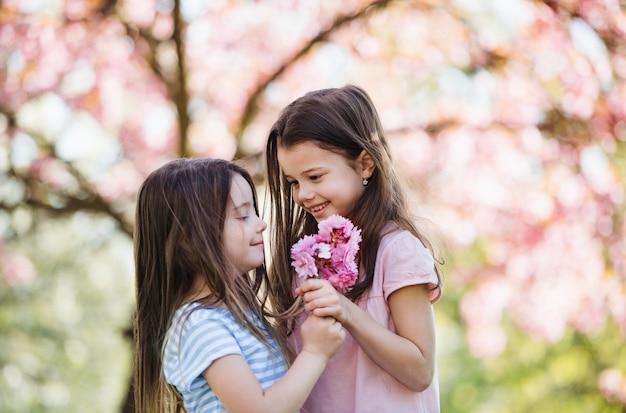 Deux petites filles debout dehors dans la nature printanière, tenant des fleurs. espace de copie.