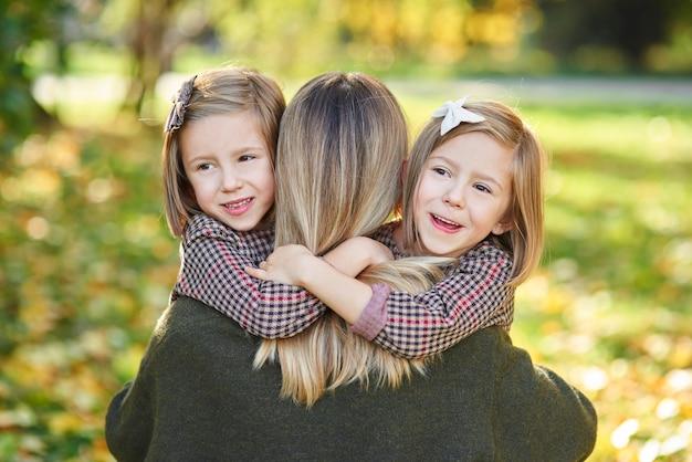 Deux petites filles embrassant leur maman