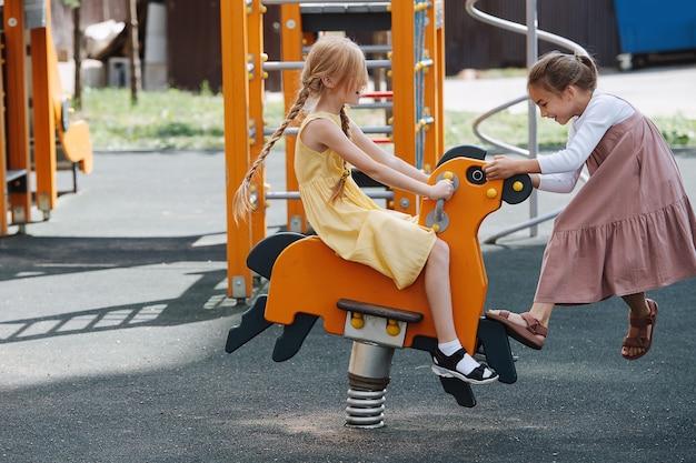 Deux petites filles heureuses jouant avec un cheval de ressort sur une aire de jeux pour enfants