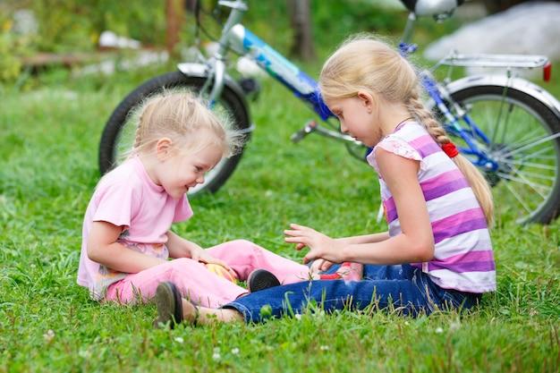 Deux petites filles jouant dans l'herbe avec le ballon contre le vélo