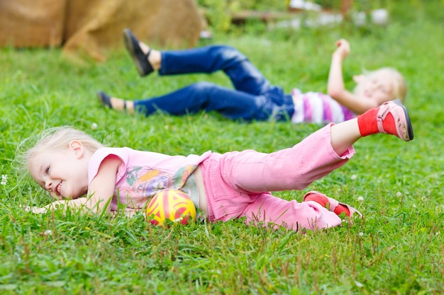 Deux petites filles jouant dans l'herbe avec le ballon