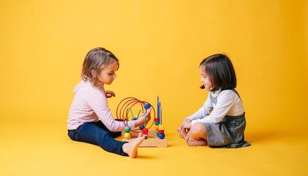 Deux petites filles jouant avec des jouets sur un fond isolé jaune