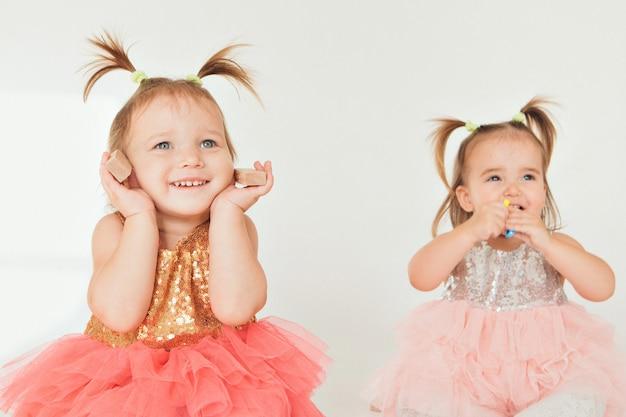 Deux petites filles jouant sur le sol sur un fond blanc