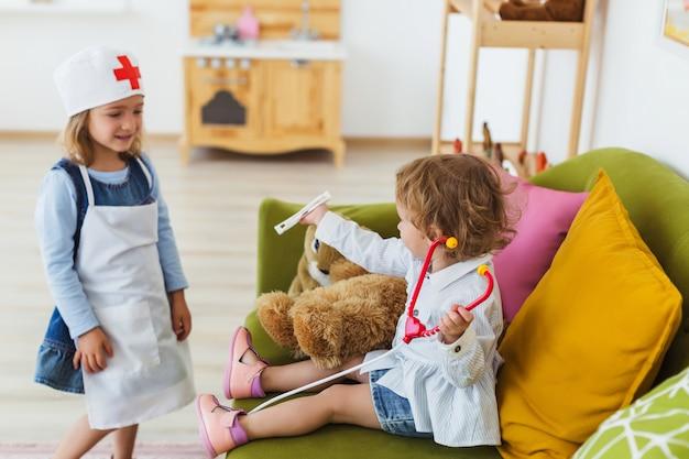 Deux petites filles jouent au docteur dans une pièce confortable.