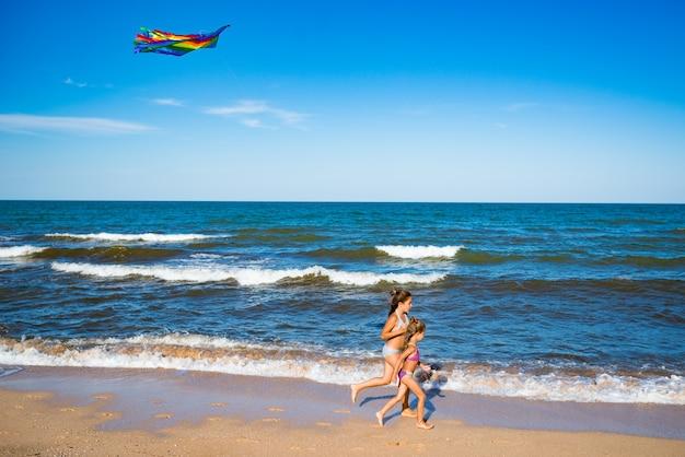 Deux petites filles joyeuses et joyeuses courent avec un cerf-volant sur le rivage sablonneux au bord de la mer. journée d'été chaude et ensoleillée. concept de jeux d'enfants actifs. espace de copie