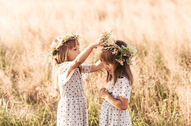 Deux petites filles jumelles identiques heureuses jouant ensemble dans la nature en été. concept d'amitié et de jeunesse entre filles. mode de vie des enfants actifs.