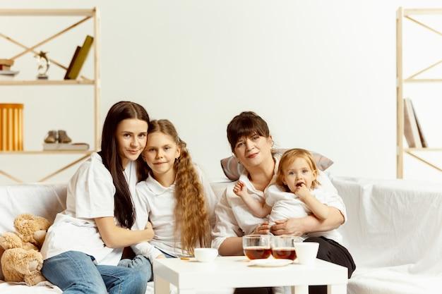 Deux petites filles leur jolie jeune mère et leur charmante grand-mère assise sur un canapé et passant du temps ensemble à la maison. génération de femmes. journée internationale de la femme. bonne fête des mères.