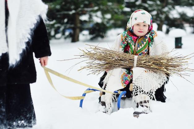 Deux petites filles avec des manteaux de fourrure et des châles dans le style russe sont transportées sur une luge brassée de broussailles
