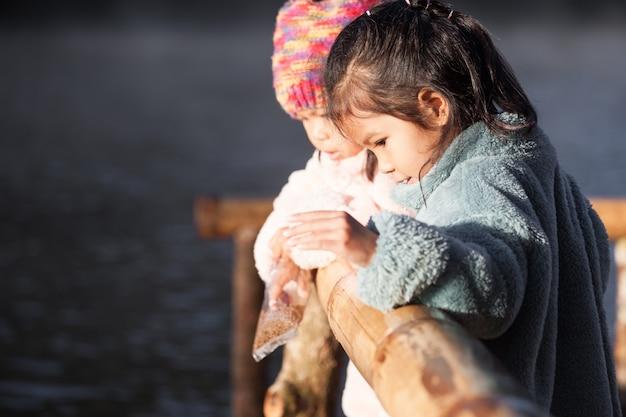 Deux petites filles mignonnes asiatiques s'amuser à nourrir et donner de la nourriture pour pêcher dans le lac