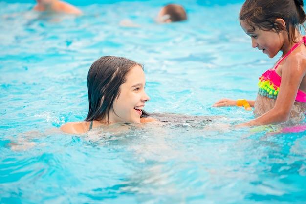 Deux petites filles mignonnes de soeurs nagent dans la piscine