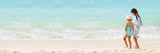 Deux petites filles sur la plage de sable par derrière