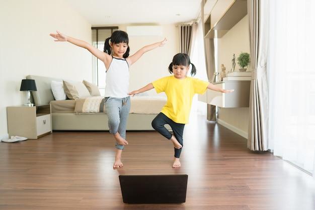 Deux petites filles pratiquant le yoga, les étirements, le fitness par vidéo sur ordinateur portable.