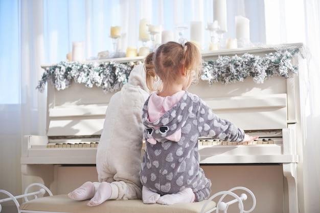 Deux petites filles en pyjama au piano le jour de noël