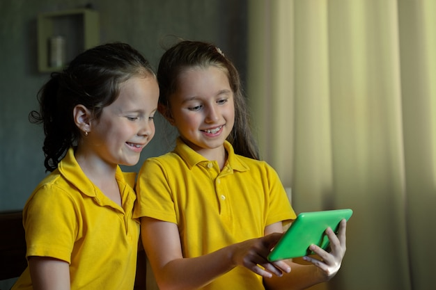 Deux petites filles regardent la tablette et rient