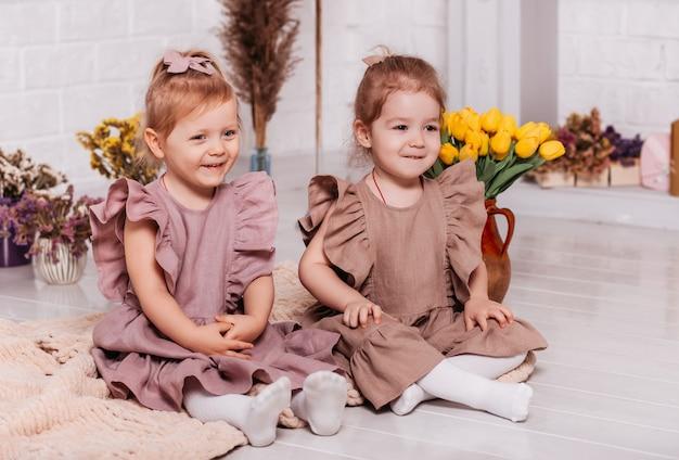 Deux petites filles en robes identiques sont assises sur le sol avec des fleurs