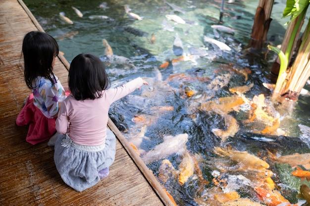 Deux petites filles s'amusant à nourrir les poissons koi