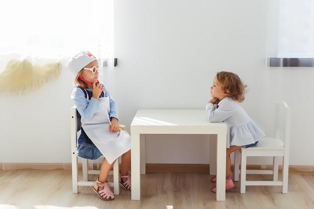 Deux petites filles s'asseoir à la table et jouer au docteur dans une chambre confortable près de la fenêtre