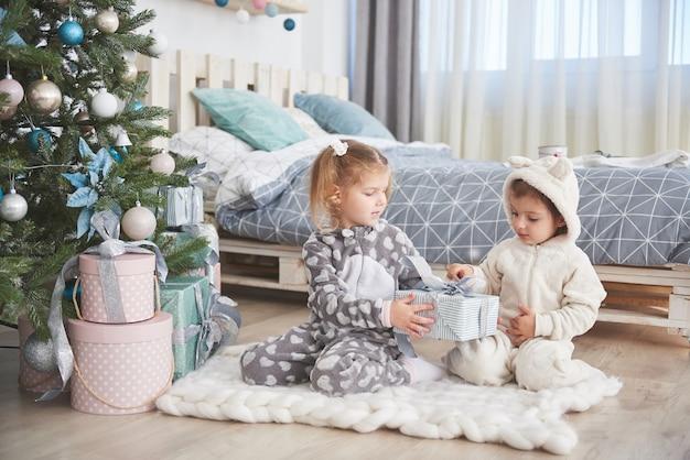Deux petites filles sœurs ouvrent leurs cadeaux à l'arbre de noël le matin sur le pont