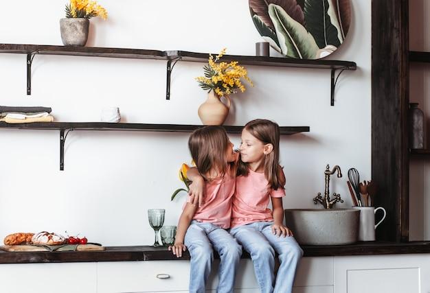 Deux petites filles sœurs s'amusent ensemble dans la cuisine